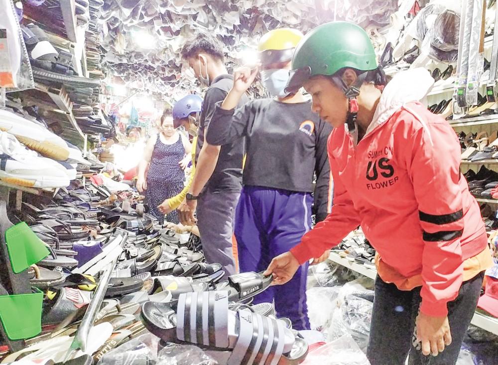 Người tiêu dùng chọn mua giày dép tại một cửa hàng ở chợ Cờ Đỏ, huyện Cờ Đỏ.