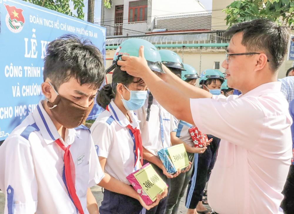 Ông Nguyễn Đức Tín, Phó Bí thư Thường trực Đảng ủy phường Trà An, quận Bình Thủy, trao học bổng, tập và nón bảo hiểm cho học sinh có hoàn cảnh khó khăn trước thềm năm học mới.
