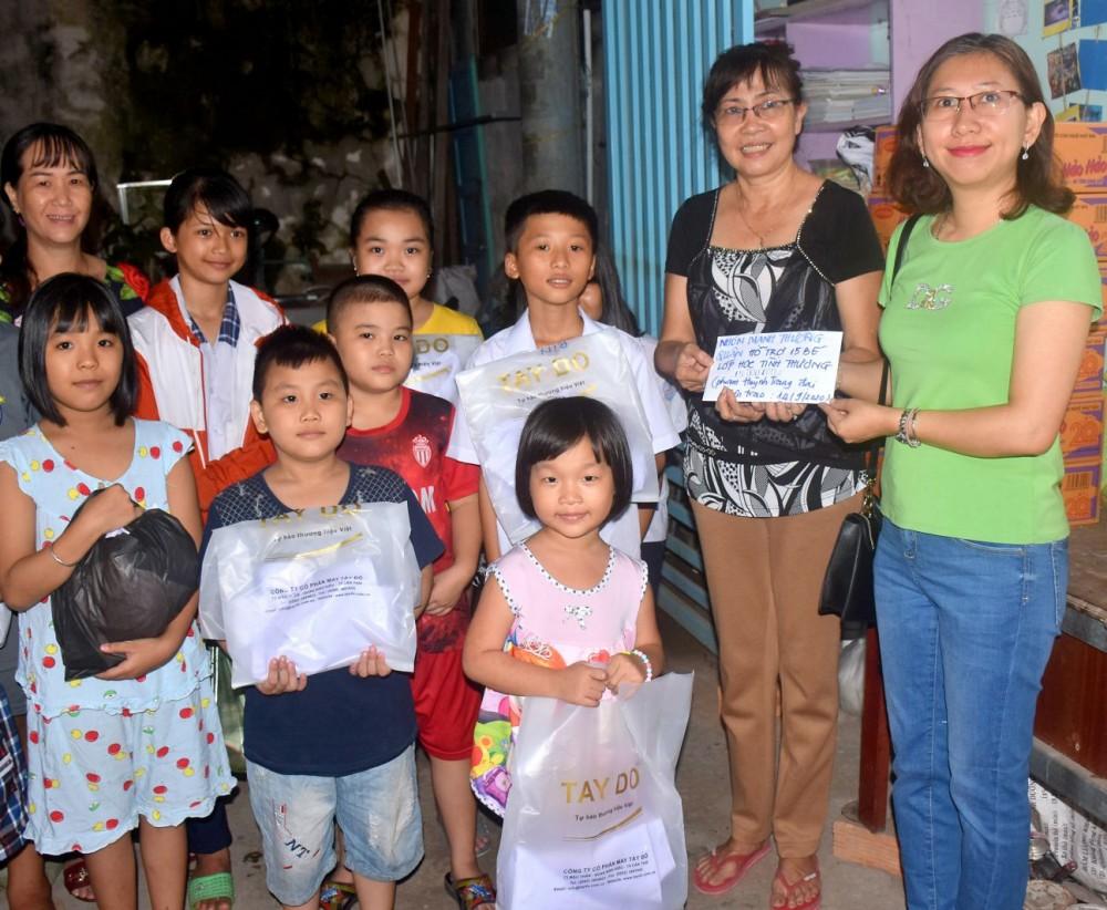 Chị Phạm Huỳnh Trang (bìa phải) trao tiền và quà cho cô trò lớp học tình thương tại phường An Cư, quận Ninh Kiều.