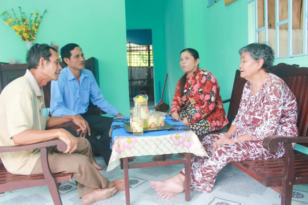 Cán bộ Mặt trận xã Trường Long thăm hỏi gia đình bà Nguyễn Thị Liêm, người tình nguyện trả sổ hộ nghèo.