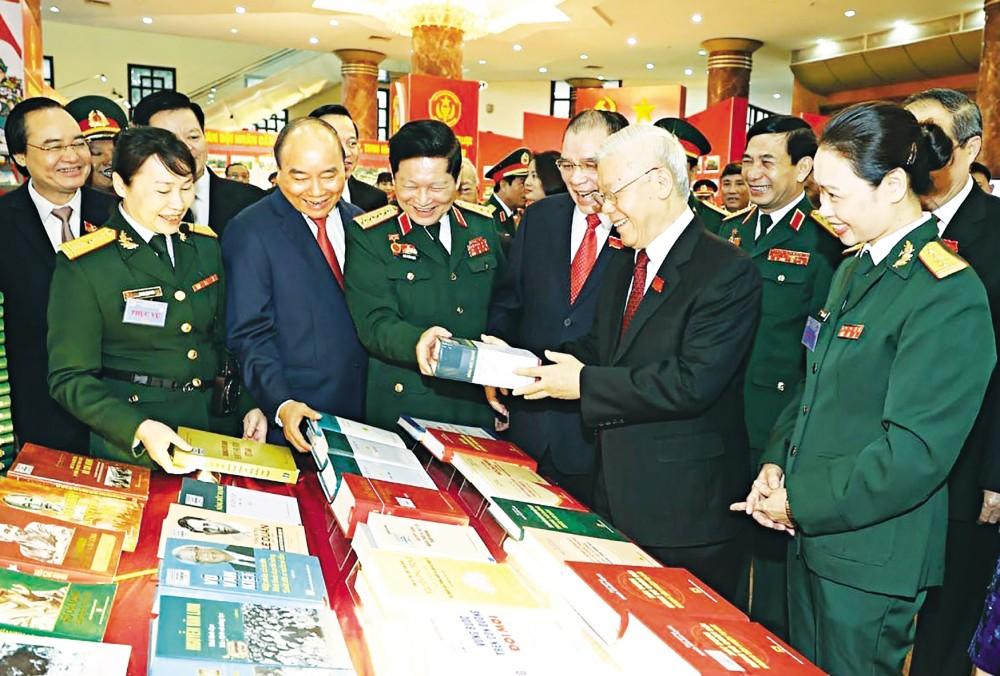 Tổng Bí thư, Chủ tịch nước Nguyễn Phú Trọng, Bí thư Quân ủy Trung ương và các đại biểu thăm gian trưng bày các ấn phẩm quốc phòng. Ảnh: Trí Dũng - TTXVN
