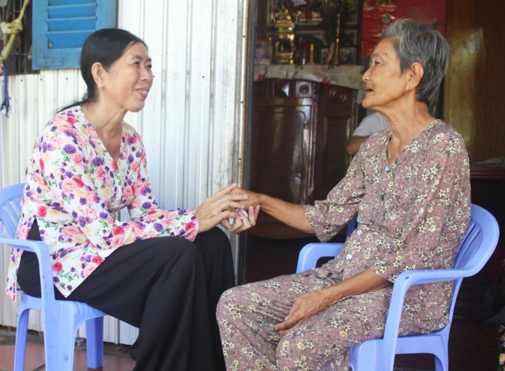 Bà Phạm Hoàng Phượng, Trưởng Ban CTMT ấp Nhơn Thọ 2 (bên trái), thăm hỏi, tìm hiểu đời sống người dân trong ấp.