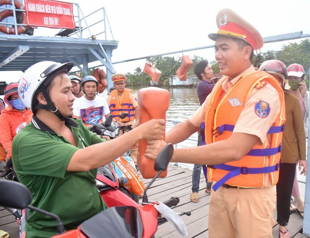 CSGT-TT Công an huyện Phong Điền trực tiếp hướng dẫn người đi đò cách sử dụng dụng cụ nổi cứu sinh cầm tay khi đi trên phương tiện thủy.