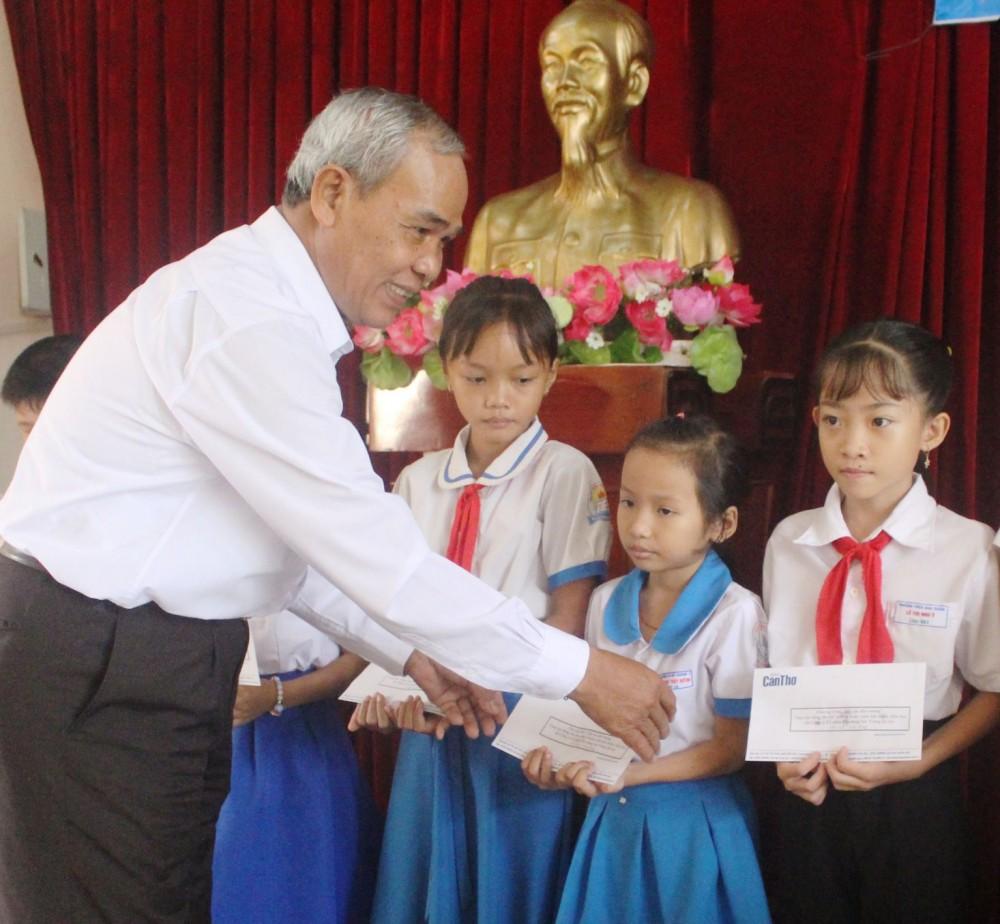 Ông Thạch Khên, nguyên Phó Tổng Biên tập Báo Cần Thơ, trao học bổng cho các em học sinh.