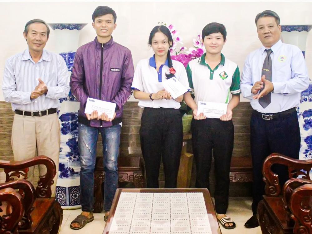 Đại diện Ban Biên tập Báo Cần Thơ (bìa trái) và ông Phạm Ngọc Gác, Phó Tổng Giám đốc Công ty CP Xây dựng Sóc Trăng trao học bổng cho các sinh viên vượt khó.