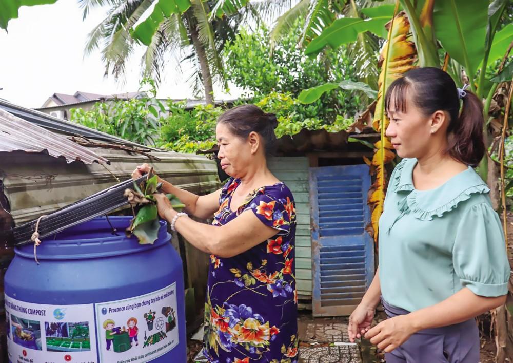 Cô Cánh (trái) giới thiệu thùng compost dùng ủ phân hữu cơ của gia đình.