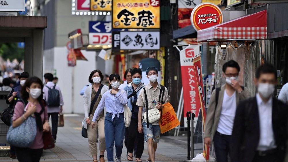 Giới trẻ Nhật đeo khẩu trang ra đường trong mùa dịch. Ảnh: AFP