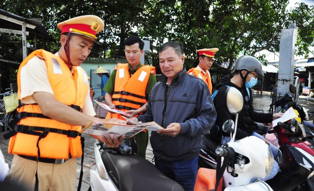Lực lượng Trạm Cảnh sát đường thủy Thới An phát tờ rơi tuyên truyền cho hành khách bến đò Rạch Nọc, phường Phước Thới, quận Ô Môn.