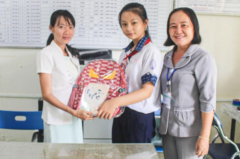 Cán bộ Hội LHPN phường Thường Thạnh (bìa trái), cùng đại diện Ban Giám hiệu Trường THCS Thường Thạnh trao quà cho em Vân Anh.
