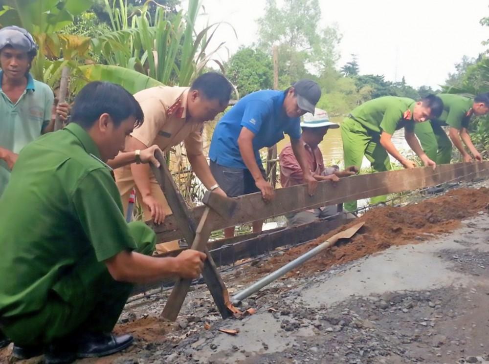 Cán bộ, chiến sĩ Chi đoàn CSGT-TT Công an quận Ô Môn và nhân dân tham gia nâng cấp, sửa chữa đoạn đường thuộc khu vực Bình Hòa.