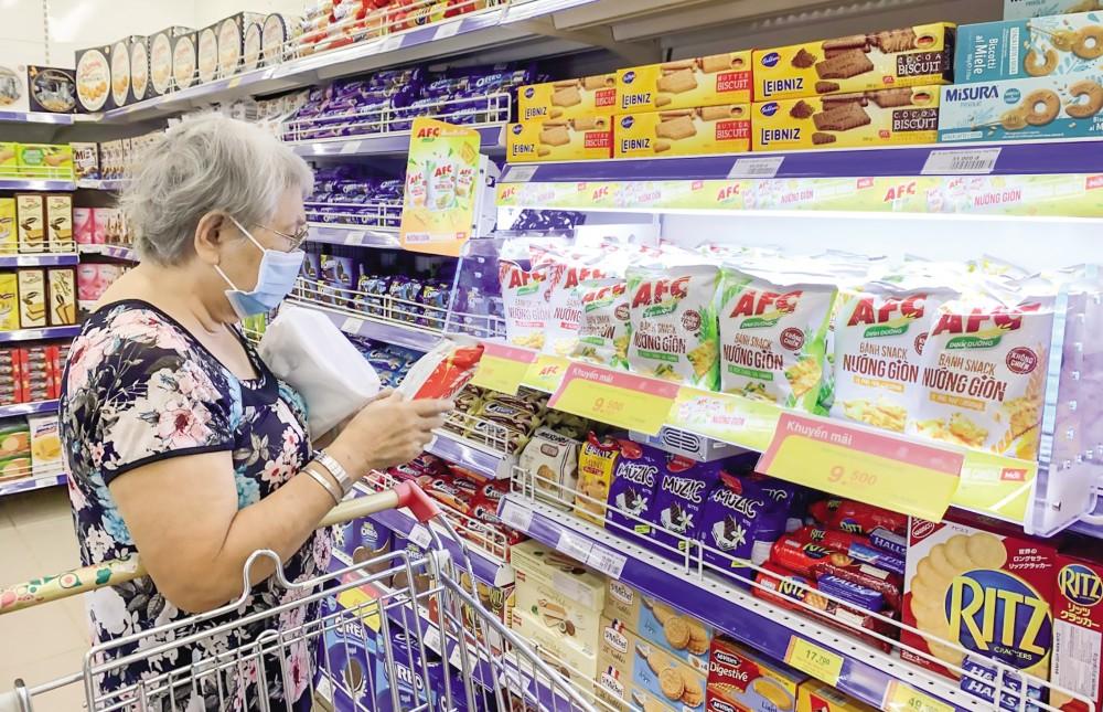 Các loại thực phẩm dinh dưỡng ăn liền được bán với đa dạng chủng loại và xuất xứ. Trong ảnh: Khách hàng chọn mua bánh dinh dưỡng ăn liền tại Siêu thị Co.opmart Cần Thơ.