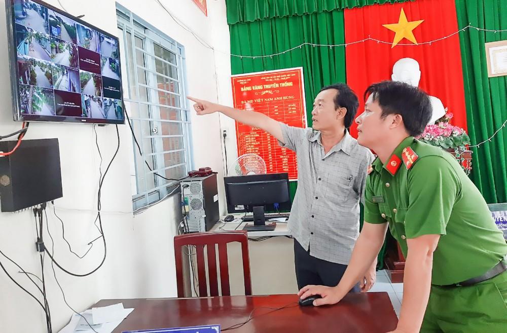Ông Nguyễn Văn Dũng (bên trái) theo dõi hoạt động của các camera an ninh.