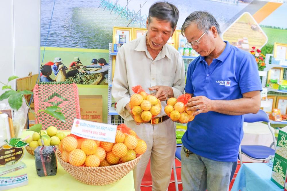 Ông Nguyễn Hữu Công  (bên trái) trưng bày, giới thiệu trái chanh dây ngọt tại Hội chợ Nông nghiệp Quốc tế Việt Nam 2020 diễn ra tại TP Cần Thơ từ ngày 11 đến 15-11-2020.