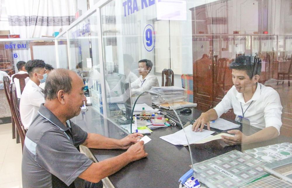Cán bộ tại Bộ phận Tiếp nhận và trả kết quả của UBND quận Ô Môn hướng dẫn thủ tục hành chính cho dân.