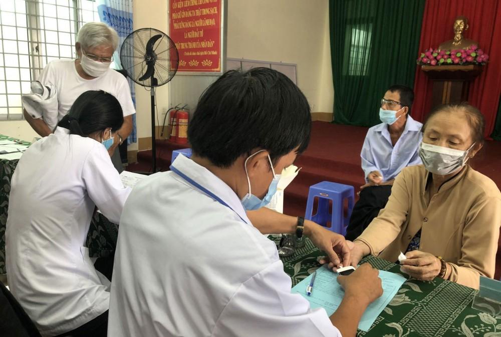 Nhân viên y tế thử đường huyết cho người dân ở quận Ninh Kiều.