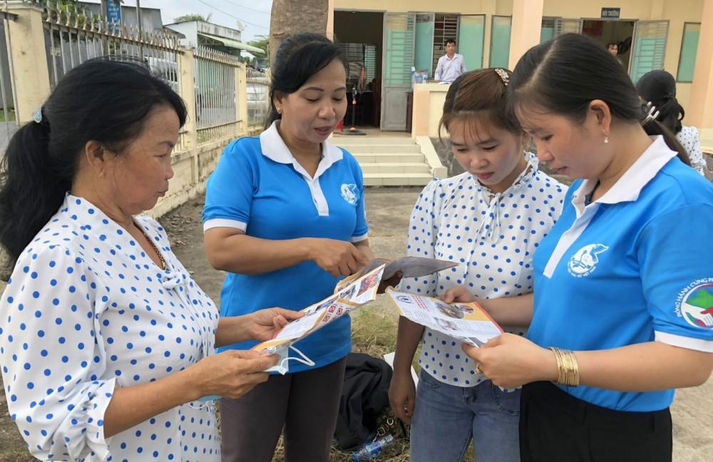 Chị Mai Tuyết Phụng, Chủ tịch Hội LHPN xã Định Môn (bìa phải) phát tờ rơi tuyên truyền TTATGT trong hội viên, phụ nữ.
