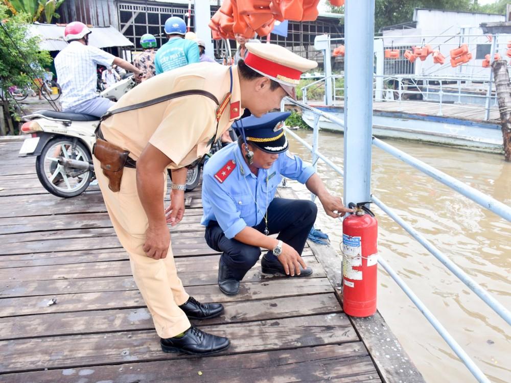 CSGT-TT Công an huyện Vĩnh Thạnh và Thanh tra giao thông huyện kiểm tra bình chữa cháy được trang bị trên phương tiện vận chuyển hành khách ngang sông.