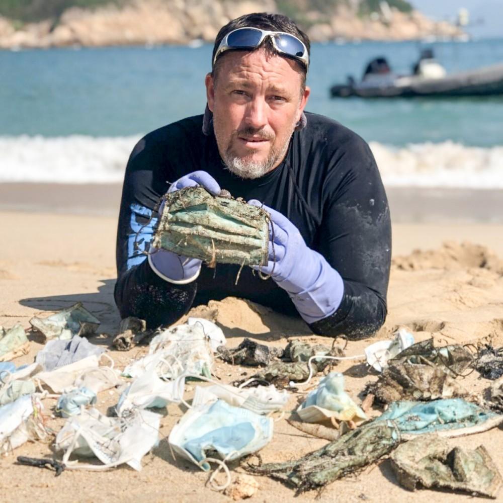 Ông Gary Stokes cùng với số khẩu trang được nhặt tại một bờ biển. Ảnh: OceansAsia