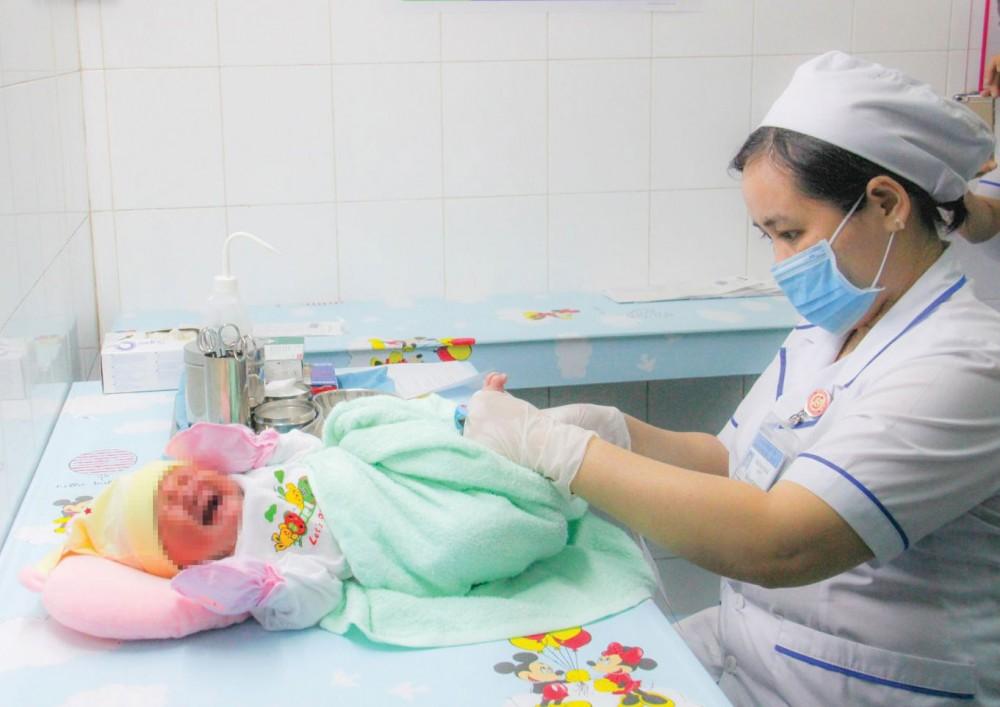 Cán bộ y tế BV Phụ sản TP Cần Thơ lấy mẫu máu khô xét nghiệm sàng lọc các bệnh ở trẻ sơ sinh.