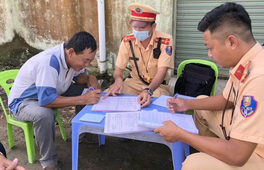 CSGT Công an huyện Cờ Đỏ hướng dẫn người vi phạm ký biên bản vi phạm hành chính.  Ảnh: KIM XUÂN