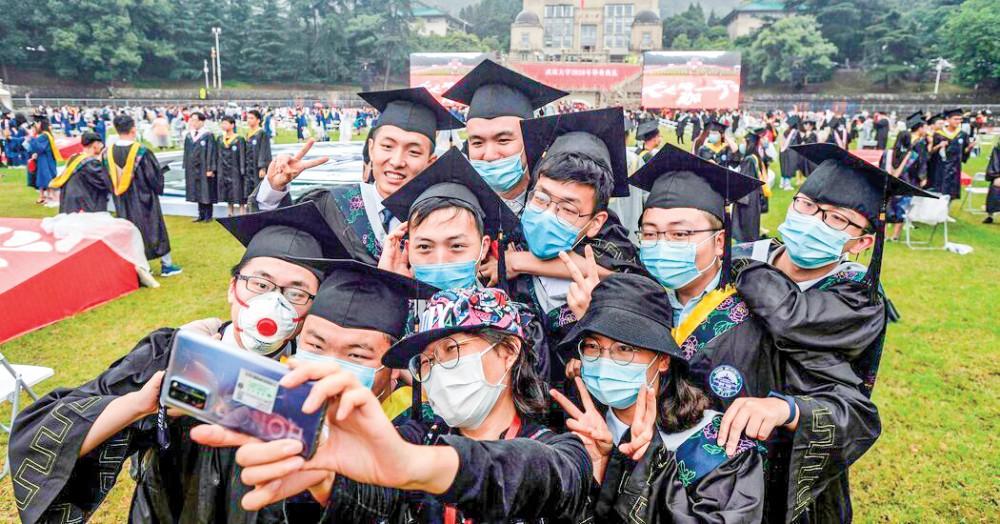 """Sinh viên Đại học Vũ Hán """"selfie"""" trong ngày tốt nghiệp. Ảnh: NYT"""