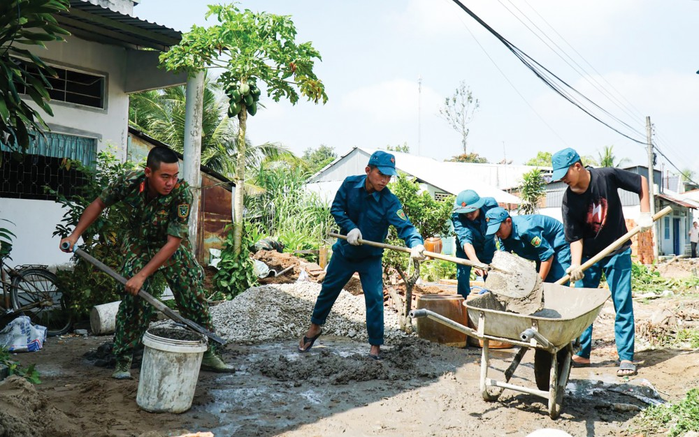 Cán bộ, chiến sĩ lực lượng vũ trang giúp gia đình cựu chiến binh Võ Thành Lễ (ở  ấp Thới Hiệp B, xã Xuân Thắng) xây dựng nhà ở.