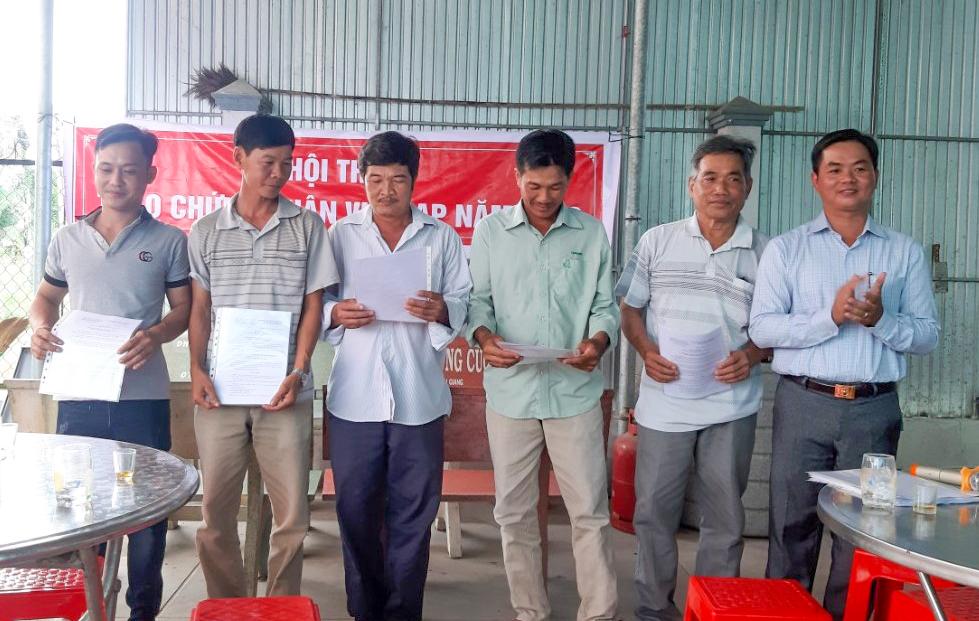 Cán bộ Trạm Khuyến nông huyện trao giấy chứng nhận đạt tiêu chuẩn VietGAP cho các xã viên HTX Tân Thới 1. Ảnh: đơn vị cung cấp