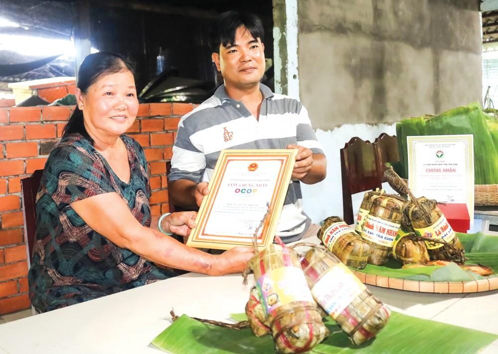 Bà Dương Thị Tuyết Nhan cùng anh Nguyễn Trung Thảo phấn khởi khi bánh tét Năm Nhan được công nhận sản phẩm OCOP đạt chuẩn chất lượng 3 sao.