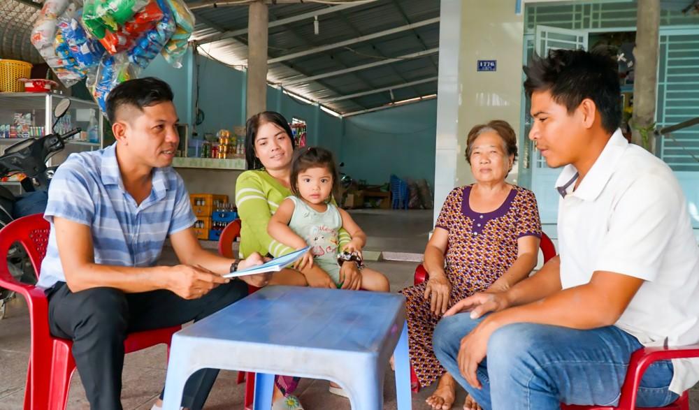 Anh Bùi Phước Thiện, Trưởng Tiểu ban Tuyên truyền của UBBC phường Long Hưng (bìa trái) tuyên truyền về cuộc bầu cử cho người dân.