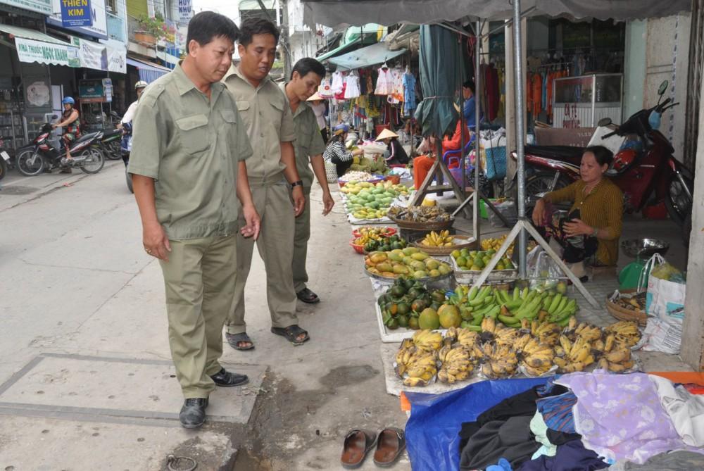 Lực lượng Ban Bảo vệ dân phố phường Thới Long kiểm tra, nhắc nhở người dân chợ Thới Long không mua bán lấn chiếm lòng, lề đường.