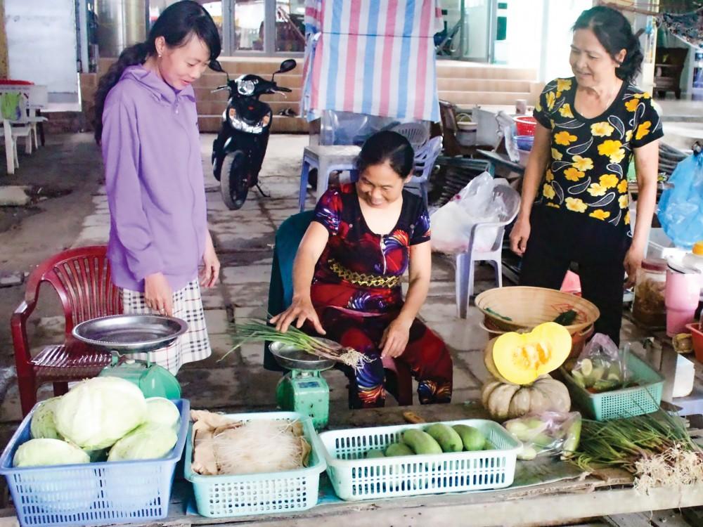 Cán bộ Hội LHPN phường Thường Thạnh (bìa trái) thăm hỏi, tìm hiểu tình hình mua bán, làm ăn của hội viên phụ nữ.