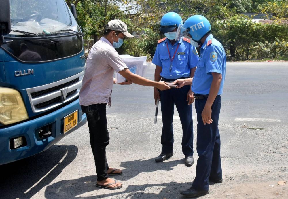 Thanh tra Sở Giao thông vận tải Cần Thơ kiểm tra hành chính đối với tài xế xe tải. Ảnh: Kim Xuân