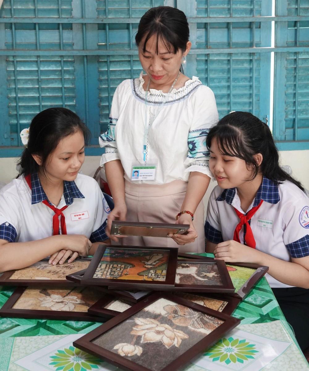 Cô Minh Trúc và Vân Anh (bìa trái), Thanh Thảo (bìa phải) xem lại các bức tranh gạo đã thực hiện.