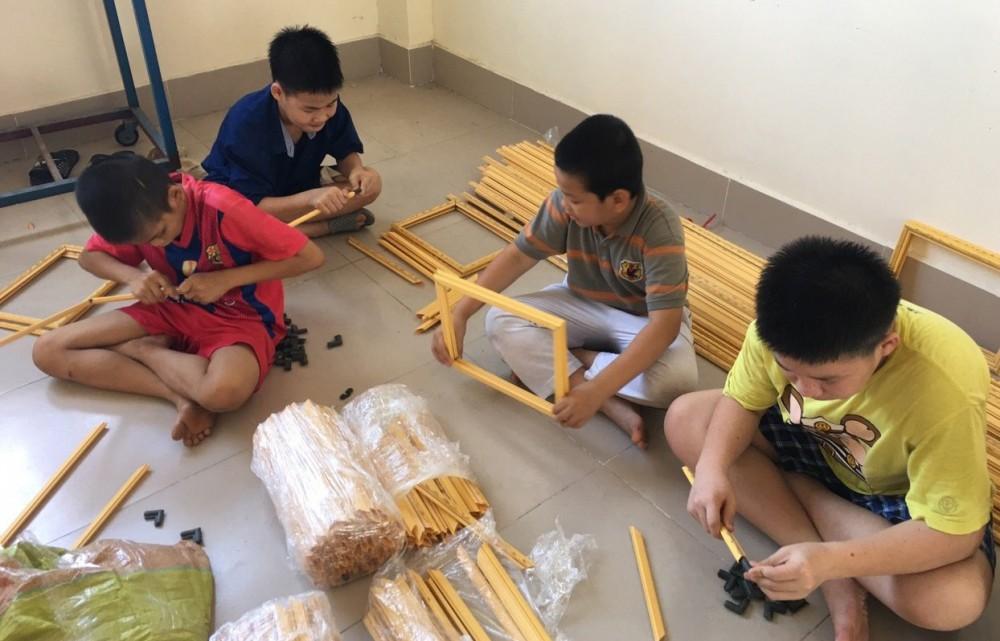 Trẻ có HCĐB tập trung thực hành nghề làm khung hình. Ảnh: CTV