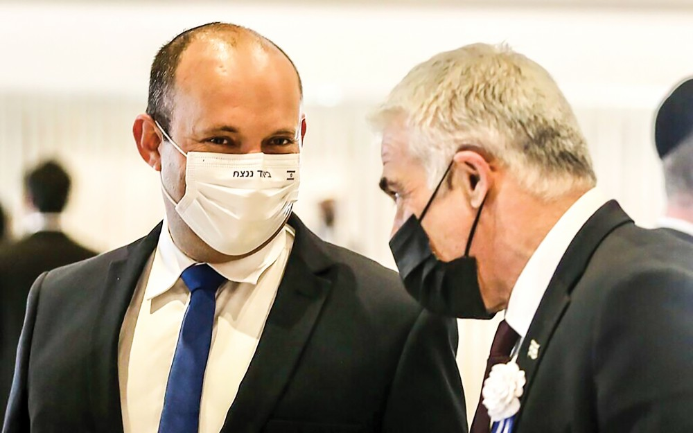 Hai ông Bennett (trái) và Lapid trao đổi tại Quốc hội Israel. Ảnh: timesofisrael