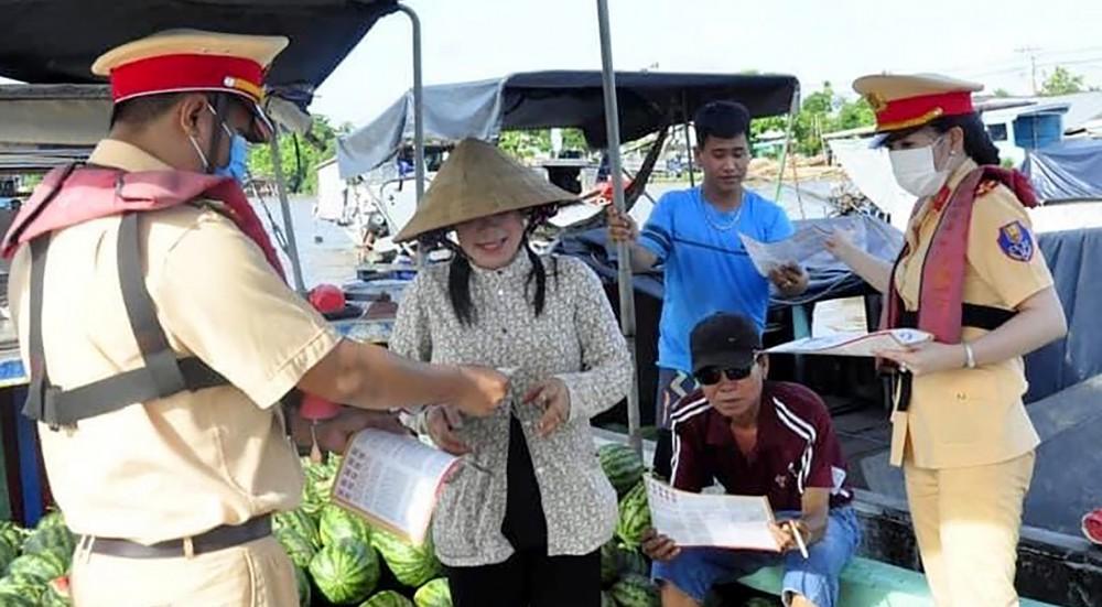 Cảnh sát đường thủy phát tờ rơi tuyên truyền ATGT ĐTNĐ cho các tiểu thương tại chợ nổi Cái Răng.