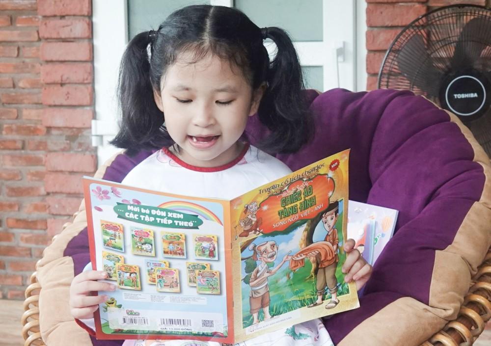 Dù chưa được học đọc, viết nhưng Anna đọc làu của cuốn truyện song ngữ Việt - Anh.