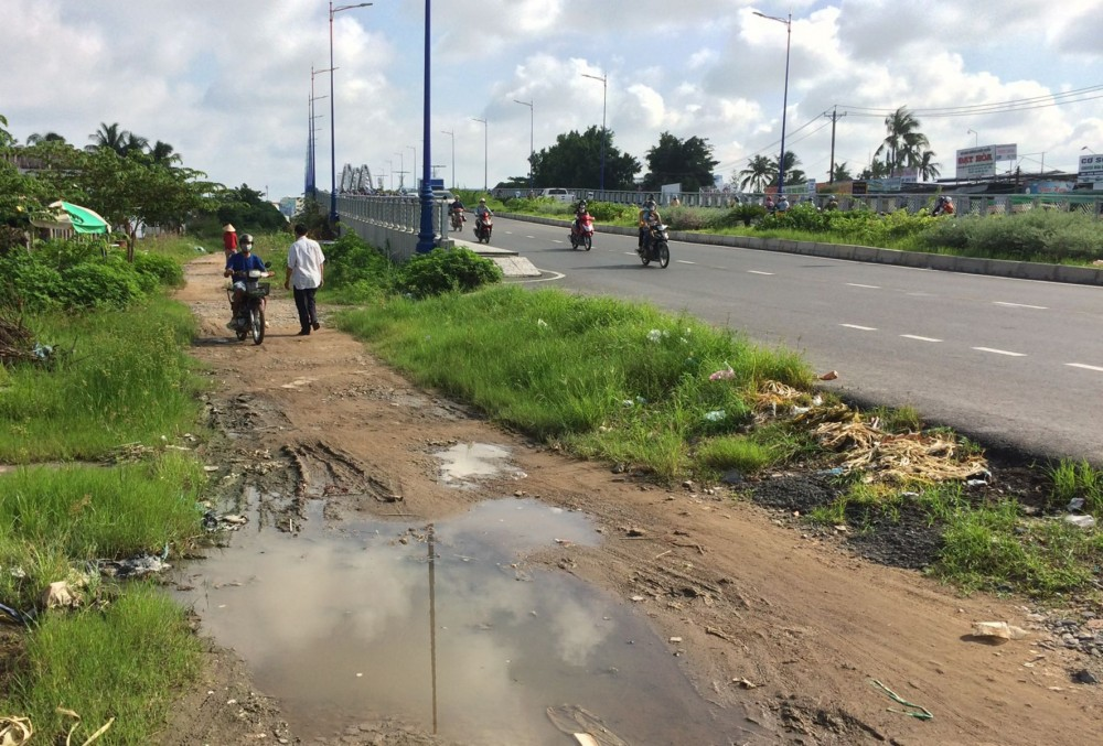 Tuyến đường dân sinh nhánh trái cầu Quang Trung chưa được nâng cấp, sửa chữa, người dân đi lại khó khăn.