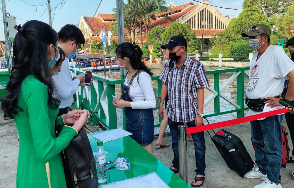 Du khách thực hiện khai báo y tế và kiểm tra thân nhiệt khi đi tuyến Cần Thơ - Côn Đảo của Mai Linh Express vào tháng 4-2021.