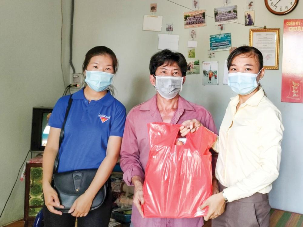 Bà Lê Thị Kiều Nương, Phó Chủ tịch Ủy ban MTTQVN phường Trà Nóc (bên phải) hỗ trợ quà cho hộ có hoàn cảnh khó khăn.