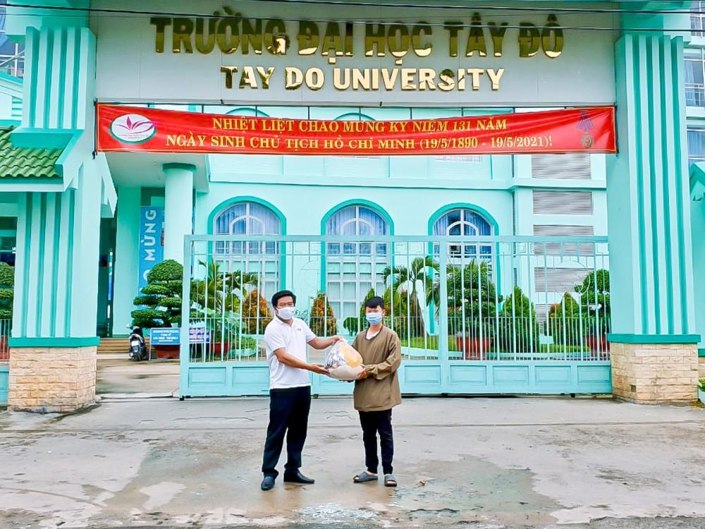 Ông Bùi Vũ Phương, Phó Ban Liên lạc HĐH (bên trái), tặng quà cho sinh viên Trường ĐH Tây Đô gặp khó khăn do dịch COVID-19.