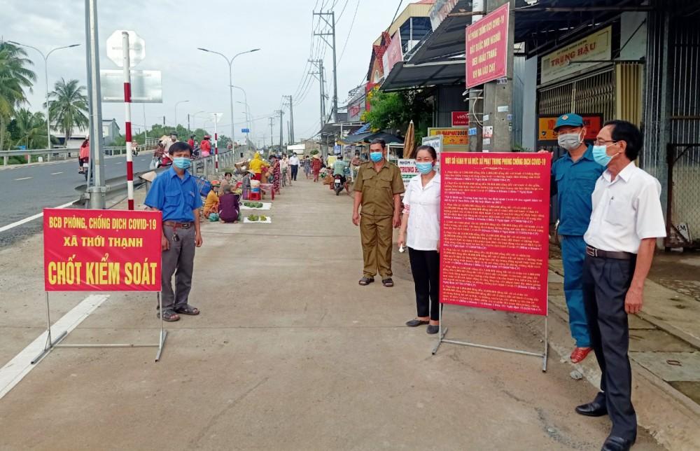Anh Nguyễn Trung Huấn (bên trái) tham gia kiểm soát và kiểm tra thân nhiệt những người vào chợ Rạch Tra.