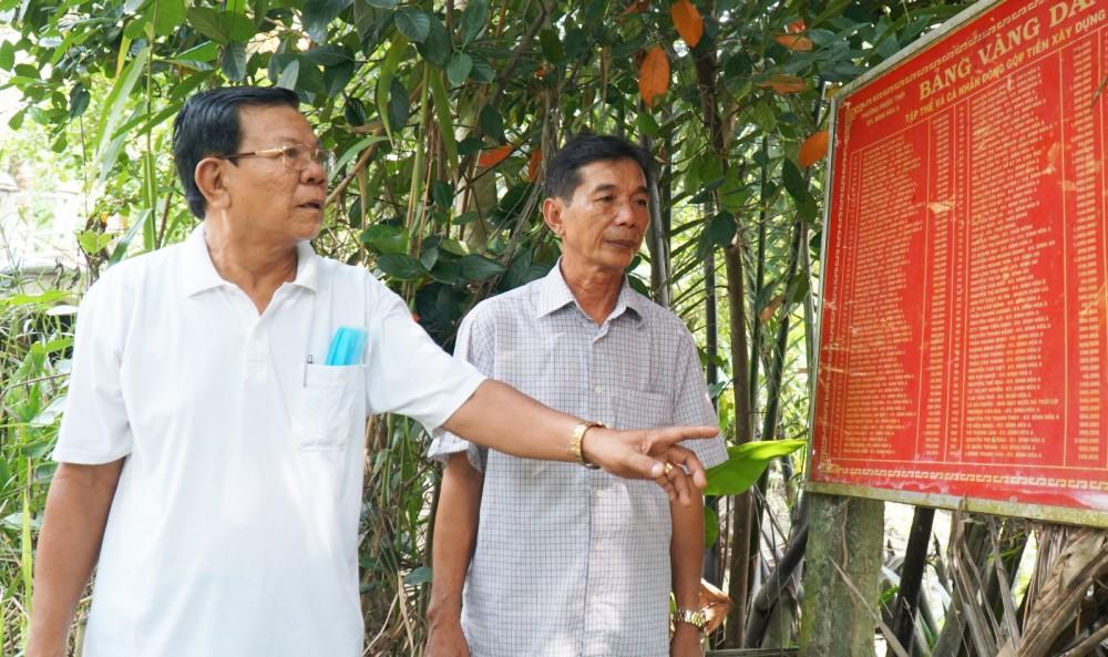 Ông Trần Quang Chánh, Bí thư Chi bộ, Trưởng khu vực Bình Hòa A, phường Phước Thới (bên trái) tích cực vận động người dân đóng góp xây dựng giao thông (ảnh chụp trong giai đoạn dịch COVID-19 chưa bùng phát và diễn biến phức tạp).