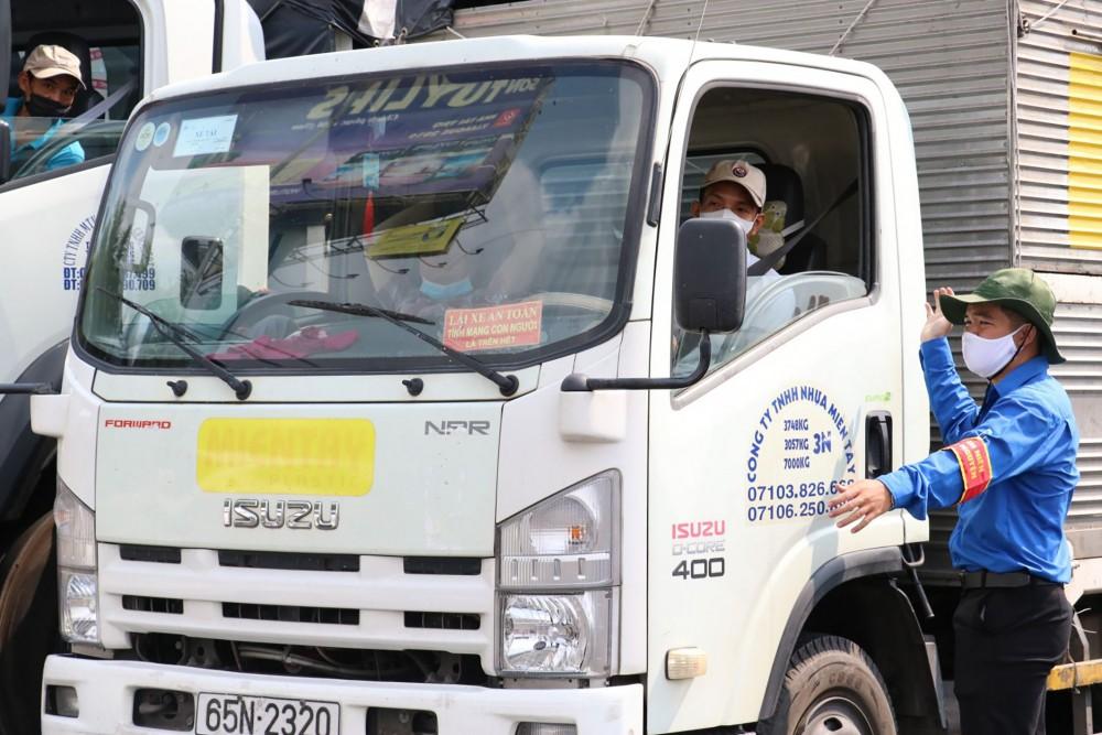 Đoàn viên tình nguyện hướng dẫn các phương tiện giao thông di chuyển đúng làn đường, thực hiện khai báo y tế tuần tự, an toàn.