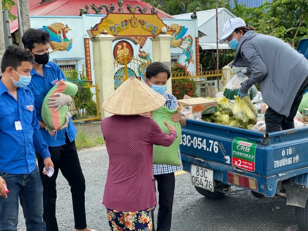 Cán bộ và đoàn viên thanh niên thị trấn Cờ Đỏ trao hỗ trợ nhu yếu phẩm cho người dân.