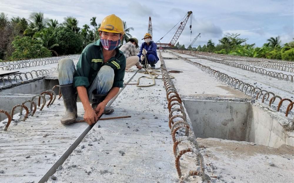 Công nhân thi công mặt cầu nhịp dẫn cầu Vàm Xáng.