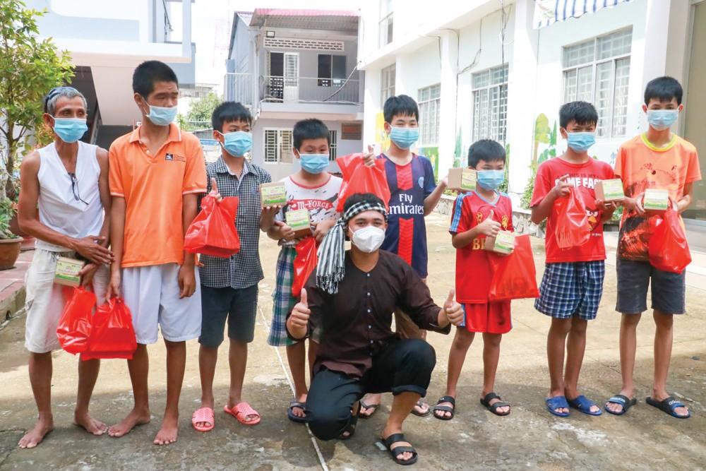 Tình nguyện viên đóng vai chú Cuội tặng quà và chụp hình lưu niệm với cháu thiếu nhi tại Trung tâm Công tác xã hội TP Cần Thơ (quận Ninh Kiều).