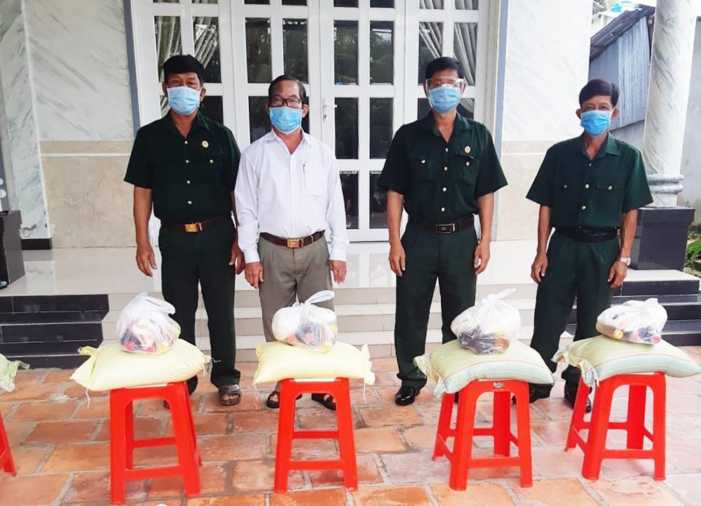 CCB Phạm Văn Nhờ (thứ hai, từ trái qua, ở xã Tân Thạnh) trao quà hỗ trợ hội viên CCB gặp khó khăn do dịch COVID-19.