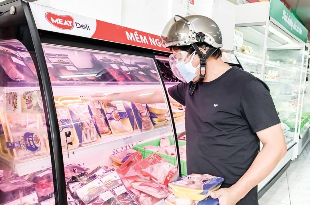 Người dân mua sắm tại cửa hàng Vinmart + trên đường Trần Hoàng Na, quận Ninh Kiều.