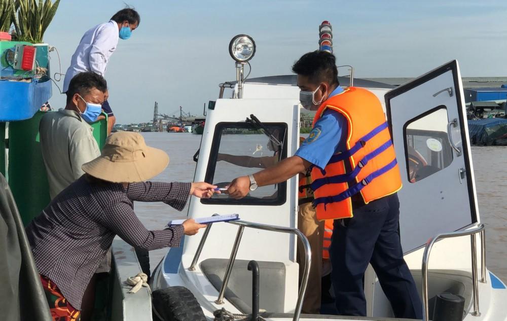 Đoàn kiểm tra liên ngành hướng dẫn người tham gia giao thông ký cam kết chấp hành nghiêm quy định của Luật Giao thông đường thủy nội địa và quy định phòng, chống dịch COVID-19.